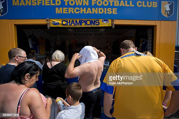 Mansfield Town supporters trying on their team's new strips at a kiosk outside Field Mill stadium during an open day held for the club's supporters....