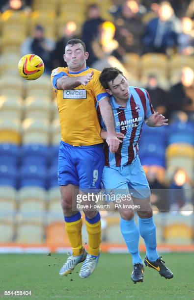 Mansfield Town's Matt Rhead and Scunthorpe United's Niall Canavan jump for the ball during the Sky Bet League Two match at the One Call Stadium...