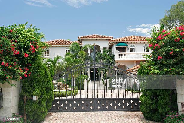 Mansion behind a gate surrounded by tropical greenery