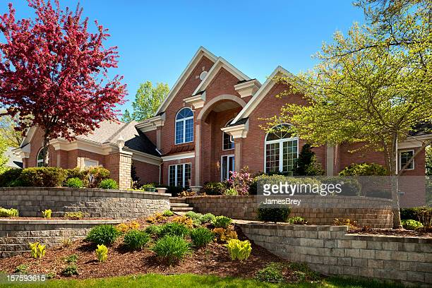 mansion home exterior design; terraced paved landscape, colorful spring foliage - brick house stock pictures, royalty-free photos & images