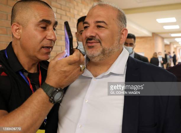 Mansour Abbas of Israel's conservative Islamic Raam party is surrounded by members of the media as he arrives to attend a parliamentary meeting at...