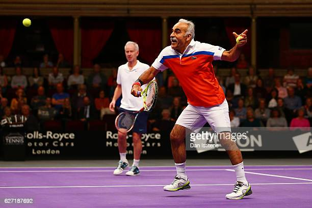 Mansour Bahrami of Iran hits a backhand volley next to his partner John McEnroe of the United States during their doubles match against Henri Leconte...