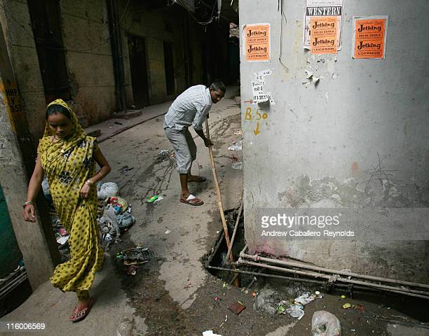 Manta a tuberculosis patient walks past a man cleaning open drainages as she goes to an operation ASHA treatment center on June 1 in New Delhi India...