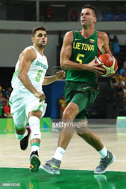 Mantas Kalnietis of Lithuania drives the ball past Raulzinho Neto of Brazil during a Men's preliminary round basketball game between Brazil and...