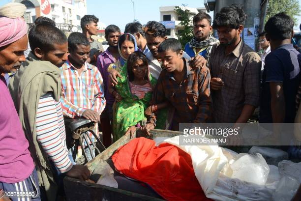 Mantu Devi and her son Anil Kumar brother of Satish Kumar who was killed when a train ploughed into a crowd of revellers cry during a cremation...