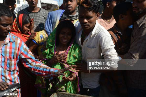 Mantu Devi mother of Satish Kumar who was killed when a train ploughed into a crowd of revellers cries during a cremation ceremony in Amritsar on...