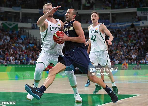 Manu Ginobili of Argentina drives to the basket against Domantas Sabonis of Lithuania and Marius Grigonis of Lithuania during the Men's Basketball...