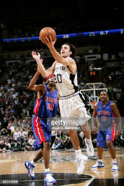 Manu Ginobili of the San Antonio Spurs drives for a shot attempt against Richard Hamilton and Lindsey Hunter of the Detroit Pistons in Game Seven of...