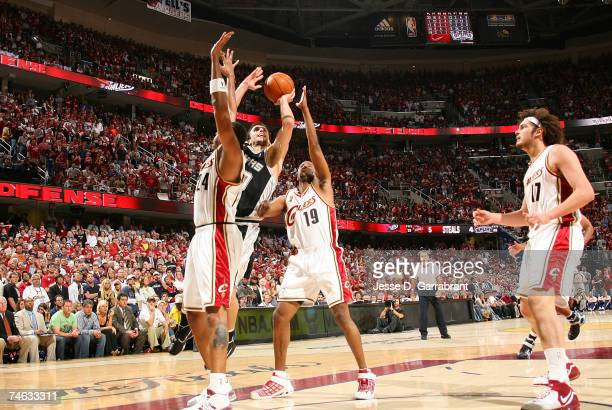 Manu Ginobili of the San Antonio Spurs drives for a shot attempt against Donyell Marshall and Damon Jones of the Cleveland Cavaliers in Game Four of...
