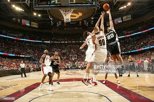 Manu Ginobili of the San Antonio Spurs drives for a shot attempt against Drew Gooden and Anderson Varejao of the Cleveland Cavaliers in Game Four of...