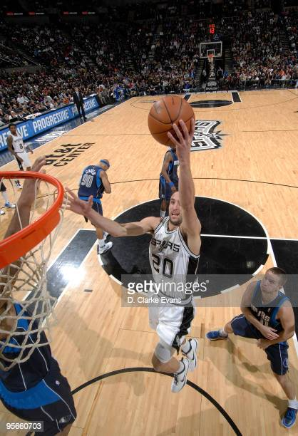 Manu Ginobili of the San Antonio Spurs dunks past Jose Juan Barea of the Dallas Mavericks on January 8, 2010 at the AT&T Center in San Antonio,...