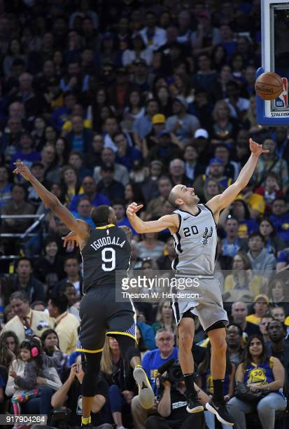Manu Ginobili of the San Antonio Spurs goes in for a layup over Andre Iguodala of the Golden State Warriors during an NBA basketball game at ORACLE...
