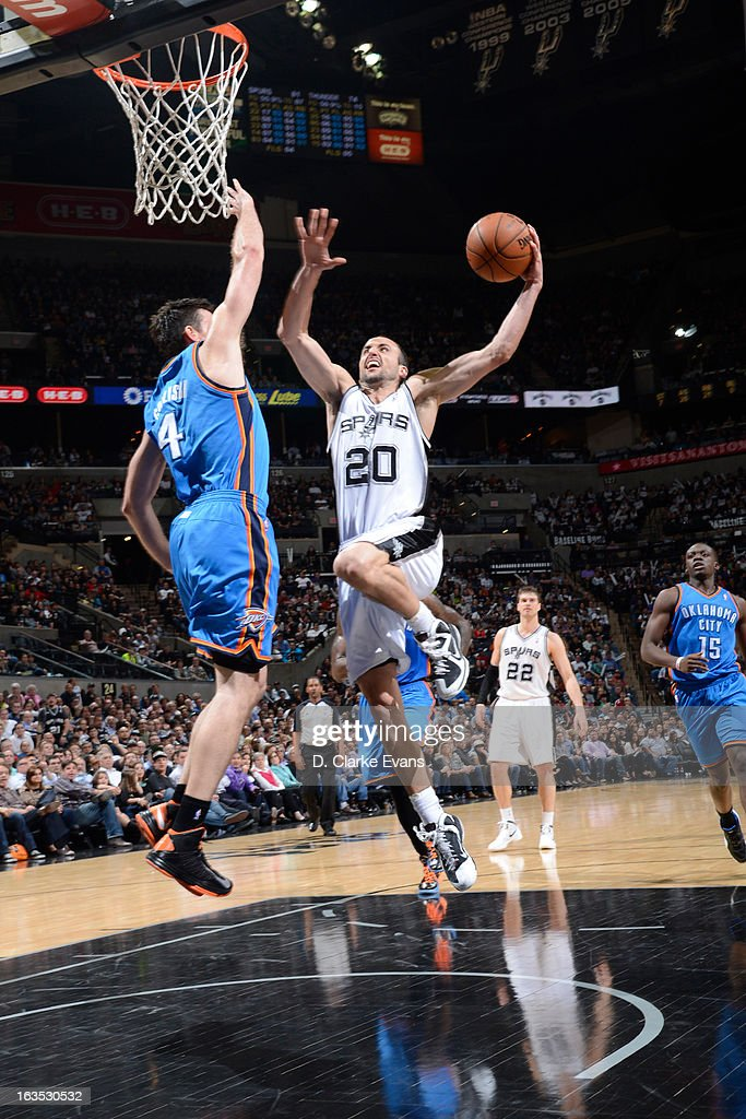 Manu Ginobili #20 of the San Antonio Spurs goes to the basket against Nick Collison #4 of the Oklahoma City Thunder on March 11, 2013 at the AT&T Center in San Antonio, Texas.