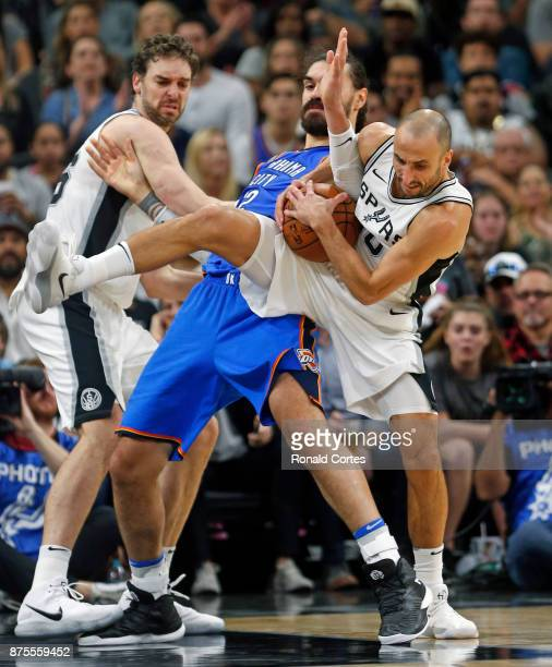 Manu Ginobili of the San Antonio Spurs grabs a rebound away from Steven Adams of the Oklahoma City Thunder at ATT Center on November 17 2017 in San...