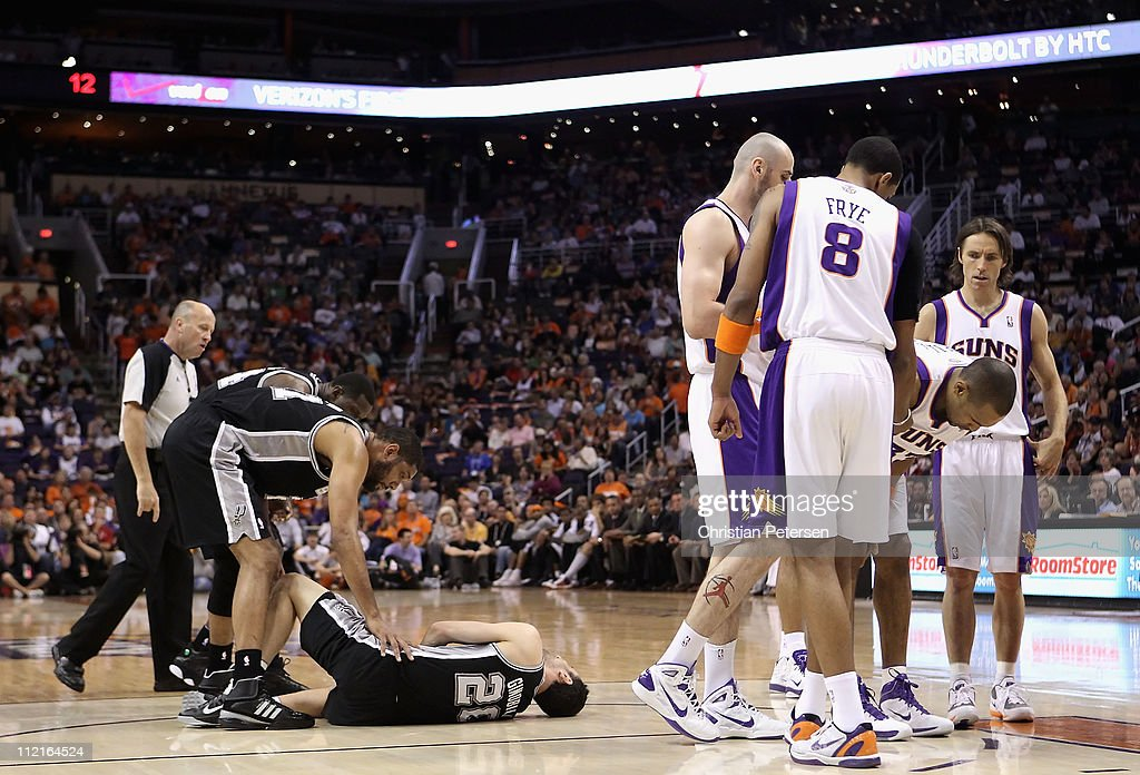 Manu Ginobili #20 of the San Antonio Spurs lays on the court in pain as teammates Tim Duncan #21 and Antonio McDyess #34 lean in following a collision with Grant Hill #33 of the Phoenix Suns during the NBA game at US Airways Center on April 13, 2011 in Phoenix, Arizona.