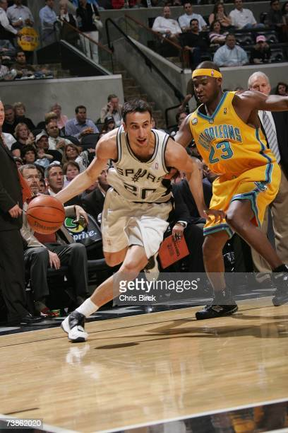 Manu Ginobili of the San Antonio Spurs moves the ball against Devin Brown of the New Orleans/Oklahoma City Hornets during the game at ATT Center on...