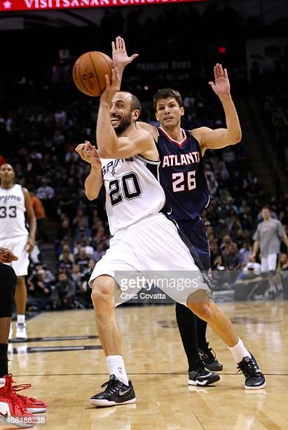 Manu Ginobili of the San Antonio Spurs passes the ball around Kyle Korver of the Atlanta Hawks at the ATT Center on November 5 2014 in San Antonio...