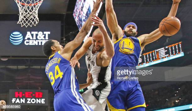 Manu Ginobili of the San Antonio Spurs tries to drive between Shaun Livingston of the Golden State Warriors and JaVale McGee of the Golden State...