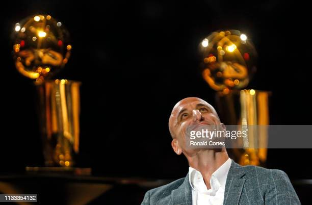 Manu Ginobili watches film on his career where his number was retired in the background are two of the four championship trophies he won with the San...