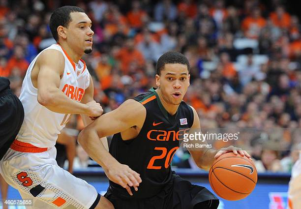 Manu Lecomte of the Miami Hurricanes drives to the basket around the defense of Tyler Ennis of the Syracuse Orange during the first half at the...