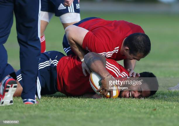 Manu Tuilagi is tackled by defence coach Andy Farrell during the British and Irish Lions training session held at Langley Park on June 3 2013 in...