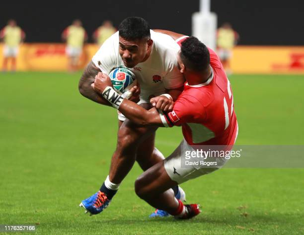 Manu Tuilagi of England breaks clear to score his first try despite being held by Cooper Vuna during the Rugby World Cup 2019 Group C game between...