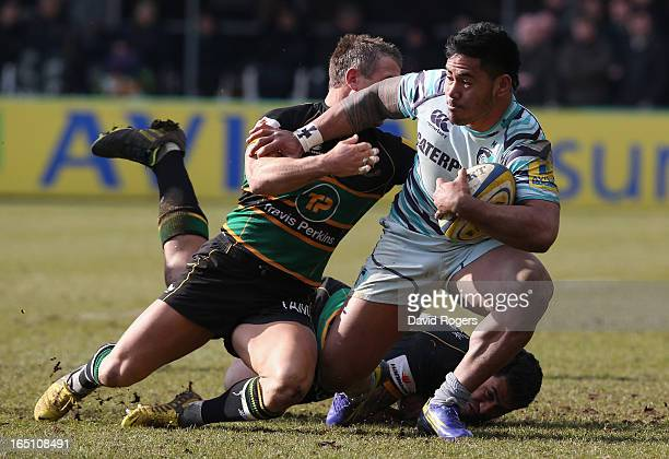 Manu Tuilagi of Leicester is tackled by George Pisi and Tom May during the Aviva Premiership match between Northampton Saints and Leicester Tigers at...