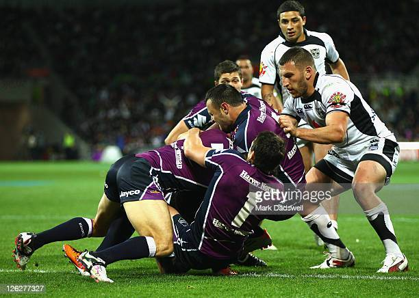 Manu Vatuvei of the Warriors is held up by the Storm during the NRL second preliminary final match between the Melbourne Storm and the New Zealand...