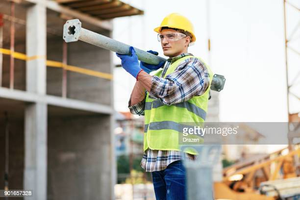 Manual construction worker working on construction platform in full safety equipment