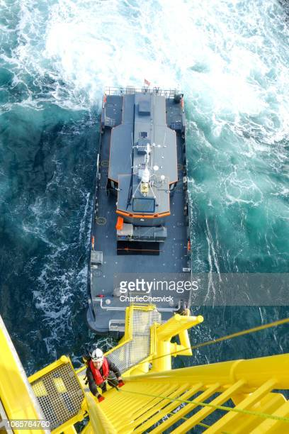 hoge arbeider offshore klimmen naar beneden van windturbine ladder en overdracht drukvat op hem wacht - reddingsvest stockfoto's en -beelden