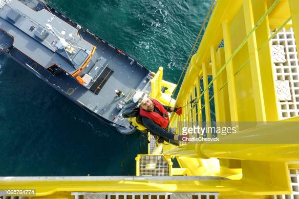 manual high worker offshore climbing  down from wind-turbine on ladder and transfer vessel in waiting for him - high up stock pictures, royalty-free photos & images