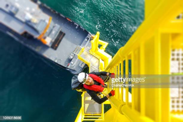 manual high worker offshore climbing on wind-turbine on ladder - wind power stock pictures, royalty-free photos & images