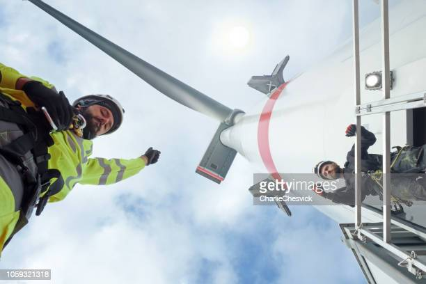manual high workers working on biggest wind-turbine - wind power stock pictures, royalty-free photos & images
