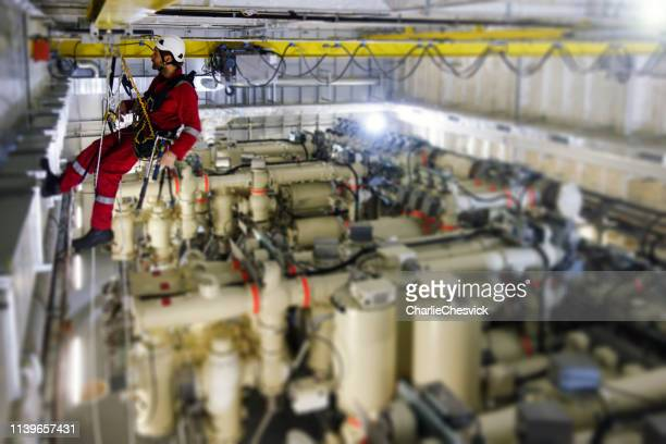 manual rope access technician making inspection of crane railing in transformer room on offshore platform - high up stock pictures, royalty-free photos & images
