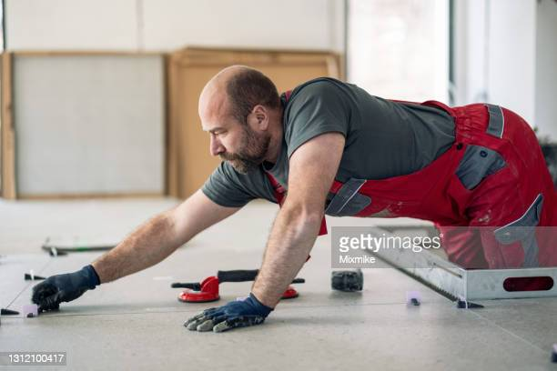 manual worker adjusting tiles - strike industrial action stock pictures, royalty-free photos & images