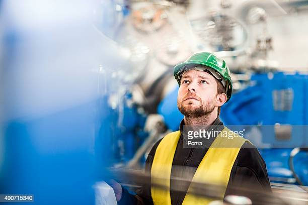 Manual worker analysing machinery in factory
