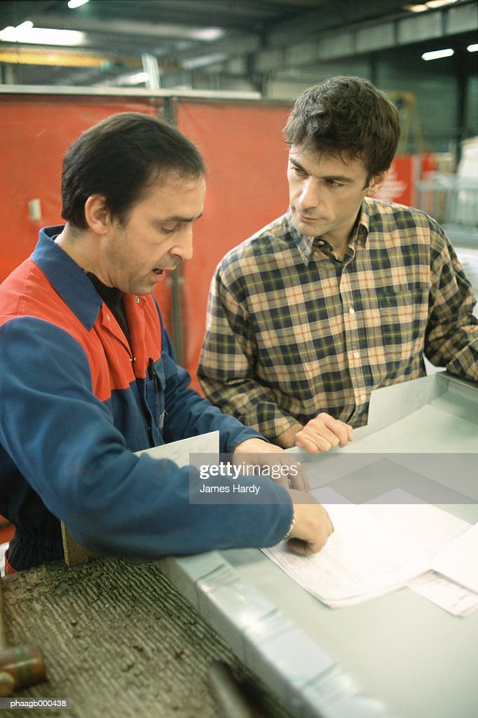 Manual worker and apprentice at work table : Stockfoto