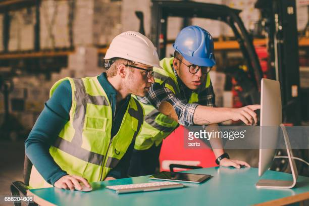Manual worker and engineer using computer in shipping warehouse