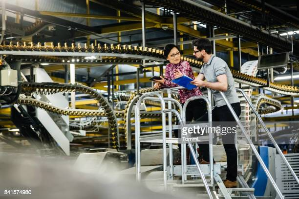 Manual Worker And Female Engineer In A Factory