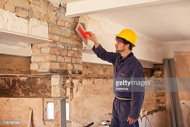 A manual worker applying plaster to a brick wall