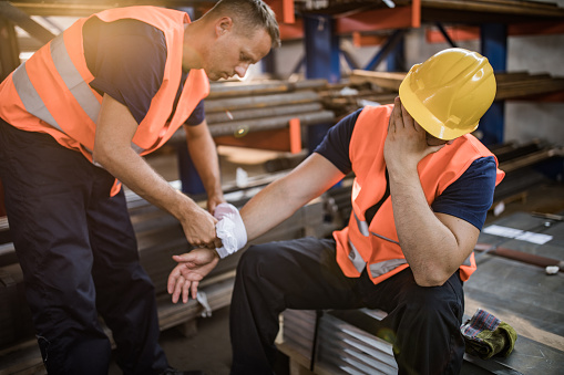 Manual worker assisting his colleague with physical injury in steel mill. 1009864426