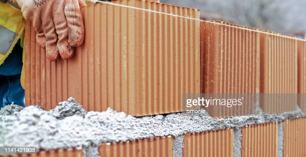 manual worker building brick wall - mattone foto e immagini stock
