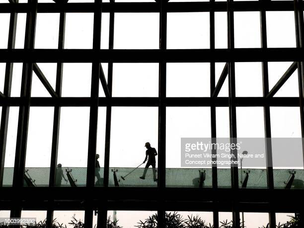 A Manual worker cleaning the Window Panes of an Airport building