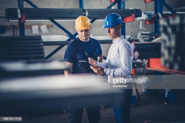 trabalhador manual, cooperando com o inspetor enquanto trabalhava em tablet digital em um armazém. - agenda eletrônica - fotografias e filmes do acervo