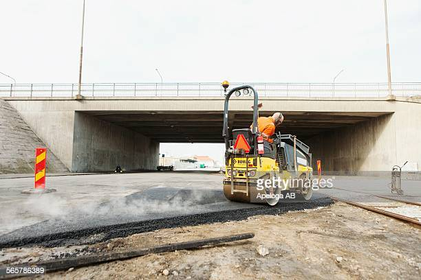 Manual worker driving steamroller on hot tar at road construction site