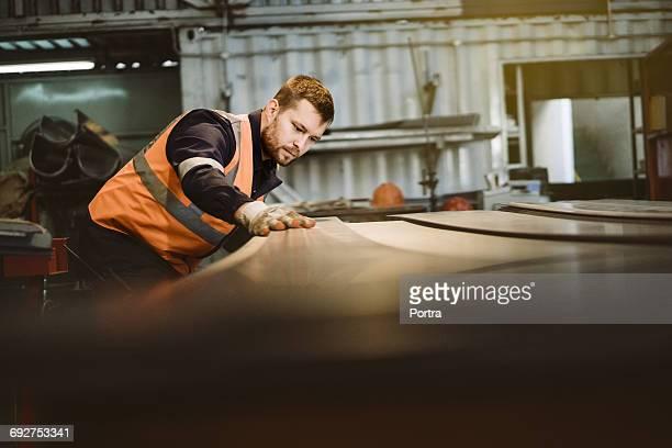 Manual worker examining sheet metal in industry