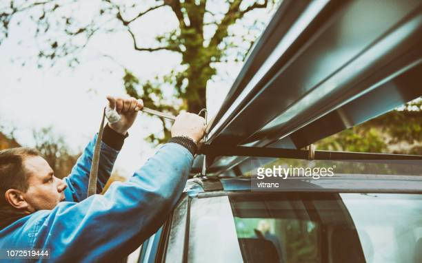 manual worker fastening sheet metal on the roof of car - metallic boot stock pictures, royalty-free photos & images