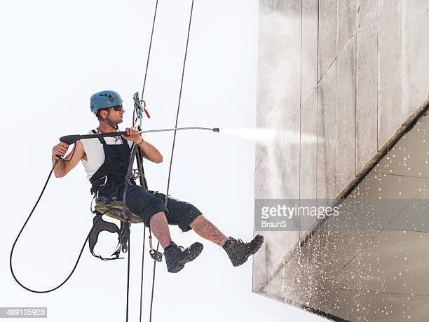 manual worker hanging high up and washing a building. - window cleaning stock photos and pictures