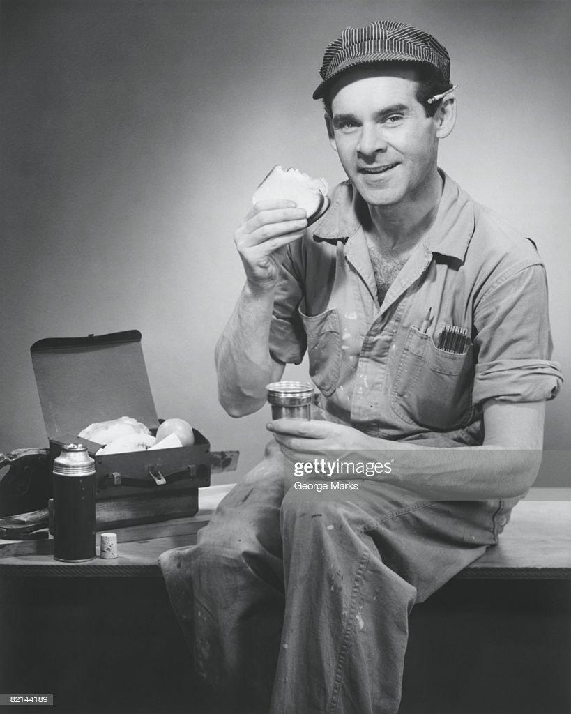 Manual worker having lunch break, (B&W), portrait : Bildbanksbilder