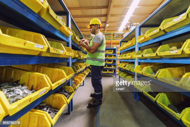 manual worker in a spare part warehouse in a factory - spare part stock pictures, royalty-free photos & images